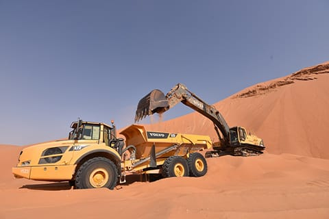 The Volvo excavator and hauler show great teamwork in the desert